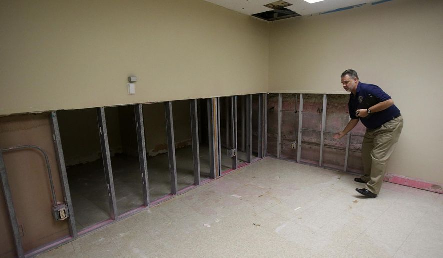 In this photo taken on Oct. 2, 2015, court administrator Michael Oakes stands in a room at the John H. Wood, Jr. Federal Courthouse, in San Antonio, Texas, that has been water damaged from a faulty sprinkler system and a malfunctioning water pipe. The leaks caused mold damage and repairs are pending on funding from the General Services Administration.  (John Davenport /The San Antonio Express-News via AP) RUMBO DE SAN ANTONIO OUT; NO SALES; MANDATORY CREDIT