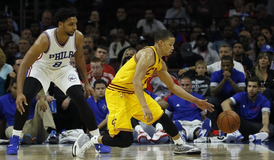 Cleveland Cavaliers' Jared Cunningham, right, chases after a loose ball as Philadelphia 76ers' Jahlil Okafor looks on during the first half of an NBA preseason basketball game, Thursday, Oct. 8, 2015, in Philadelphia. (AP Photo/Matt Slocum)
