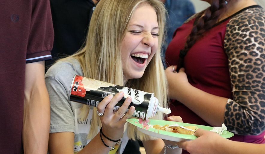 In this Oct. 5, 2015 photo, Esther Blanchet, of Limours, France, laughs after getting whipped cream all over the place while decorating her crepe at Cheyenne's East High in Cheyenne, Wyo. In the past, East High French teacher Paula Egan-Wright has taken students to France to visit and learn the French culture. This is the first time French students have visited Cheyenne in return. (Blaine McCartney/The Wyoming Tribune Eagle via AP) MANDATORY CREDIT