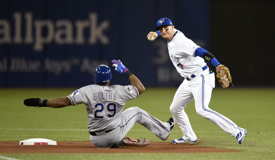 Toronto Blue Jays' shortstop Troy Tulowitzki forces out Texas Rangers' Adrian Beltre at second base before throwing to first base for the double play during the first inning in Game 1 of an American League Division Series in Toronto on Thursday, Oct. 8, 2015. (Frank Gunn/The Canadian Press via AP)