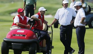 United States' J.B. Holmes, right and teammate Bubba Watson talk with team assistants Davis Love III, left, and Steve Stricker during their foursome match at the Presidents Cup golf tournament at the Jack Nicklaus Golf Club Korea, in Incheon, South Korea, Thursday, Oct. 8, 2015.(AP Photo/Woohae Cho)