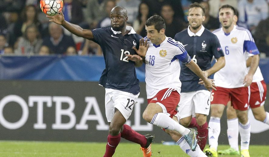 France's Lassant Diapra, left, challenges for the ball with Armenia's Henrikh Mkhitaryan during their friendly soccer match in the stadium of Nice, southeastern France, Thursday, Oct 8, 2015. (AP Photo/Lionel Cironneau)