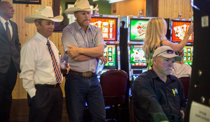 In this Thursday, Aug. 13, 2015 photo,  Rep. Bill Pownall, R-Gillette, left, and Sen. Larry Hicks, R-Baggs, watch as a man bets on historic horse races Mingles Lounge in Gillette, Wyo. The Wyoming Pari-Mutuel Commission is meeting Thursday, Oct.m8, 2015, to discuss the use of historic horse racing terminals throughout the state. The meeting Thursday comes after the commission ordered a temporary halt to the historic horse racing terminals at bars and off-track betting sites. The terminals were turned off Sunday. (Ryan Dorgan /The Casper Star-Tribune via AP) MANDATORY CREDIT