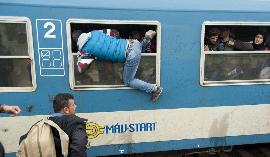 A migrant climbs out of the window of a train after he and others arrived at the railway station of Hegyeshalom, at the Austrian border, 169 km west of Budapest, Hungary, Wednesday, Oct. 7, 2015. The migrants arrived here from the Croatian border to continue their journey to Austria. (Csaba Krizsan/MTI via AP)