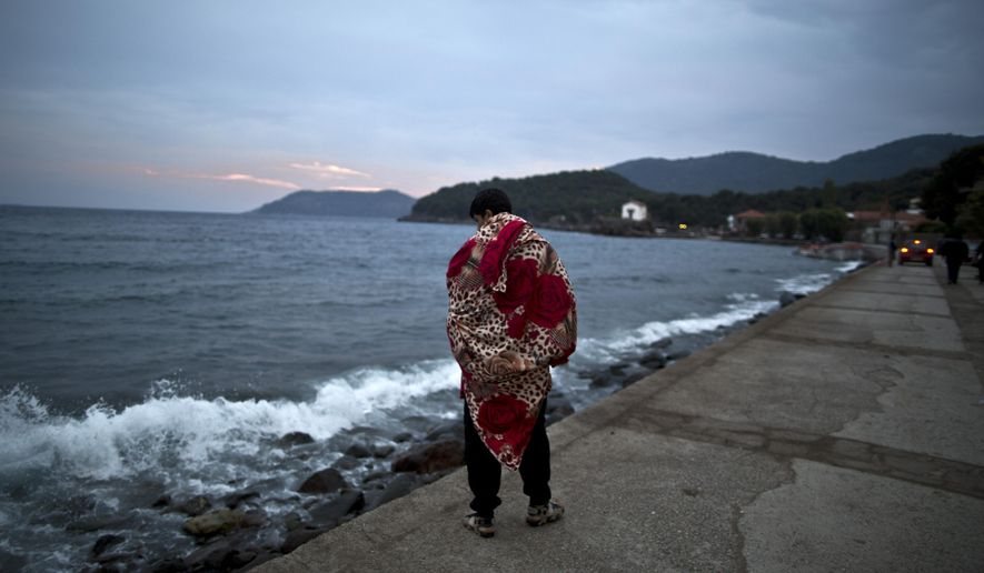 An Afghan refugee wrapped in a blanket walks by the sea after he and others arrived late in the night on a dinghy from the Turkish coast to the northeastern Greek island of Lesbos, early Thursday, Oct. 8 , 2015. More than 500,000 people have arrived in the European Union this year, seeking sanctuary or jobs and sparking the EU's biggest refugee emergency in decades. (AP Photo/Muhammed Muheisen)