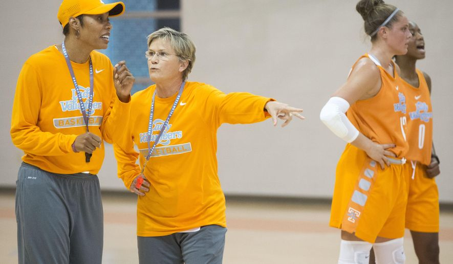 Tennessee head coach Holly Warlick, center, talks with associate head coach Kyra Elzy during NCAA college basketball practice, Thursday, Oct. 8, 2015, in Knoxville, Tenn.  The Lady Vols opened practice this week seeking to reach the Final Four for the first time since its 2008 national championship season. (Saul Young/Knoxville News Sentinel via AP)