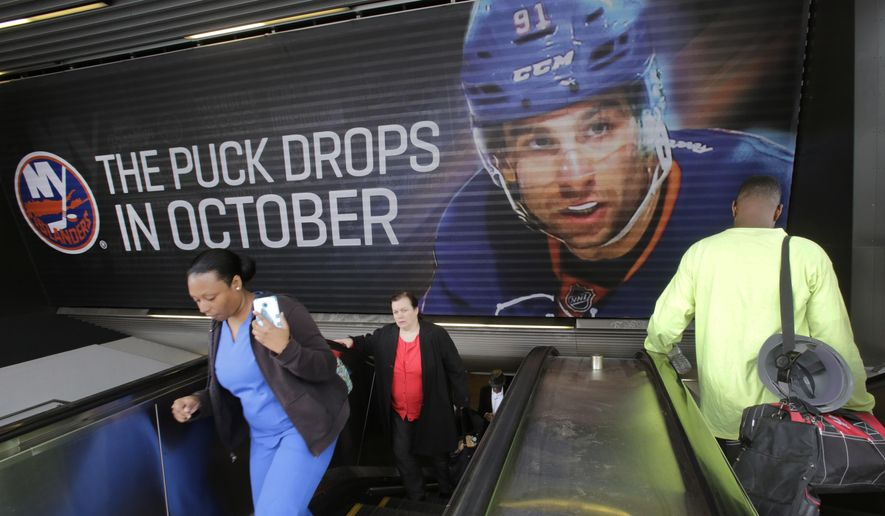 Subway passengers pass signage for the New York Islanders hockey team near the  Barclays Center, Thursday, Oct. 8, 2015 in the Brooklyn borough of New York. The Islanders, who formerly played at Nassau Coliseum in Uniondale, N.Y., will now call Brooklyn home when they open the 2015-2016 season on Friday against the Chicago Blackhawks. (AP Photo/Mark Lennihan)