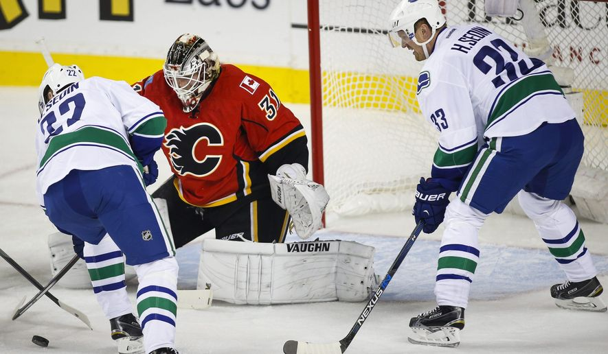 Vancouver Canucks' Daniel Sedin, left, from Sweden, tries to get the puck to his brother Henrik Sedin, right, as Calgary Flames goalie Karri Ramo, from Finland, looks on during the first period of an NHL hockey game in Calgary, Alberta, Wednesday, Oct. 7, 2015. (Jeff McIntosh/The Canadian Press via AP) MANDATORY CREDIT
