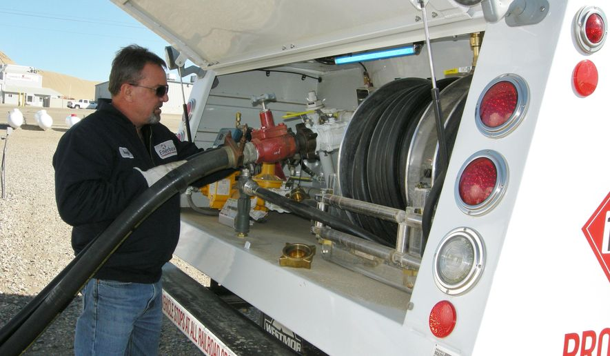 Enerbase employee Randy Thor connects hoses to fill his propane truck in Minot, N.D.,  before making more delivery calls on Sept. 28, 2015.  Propane users may be heating their homes more cheaply this winter than they have for many years. Large petroleum inventories have caused prices to plummet, and that's good news for many rural residents who heat with propane. (Jill Schramm/The Minot Daily News via AP) MANDATORY CREDIT