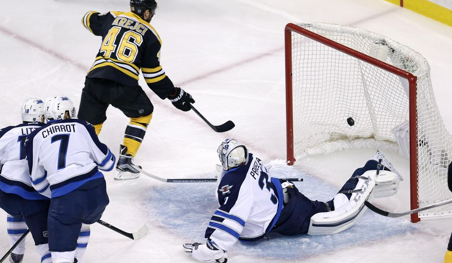 Boston Bruins center David Krejci (46) beats Winnipeg Jets goalie Ondrej Pavelec (31) for a goal during the first period of an NHL hockey game in Boston, Thursday, Oct. 8, 2015. Krejci and Pavelec are both from he Czech Republic. (AP Photo/Charles Krupa)
