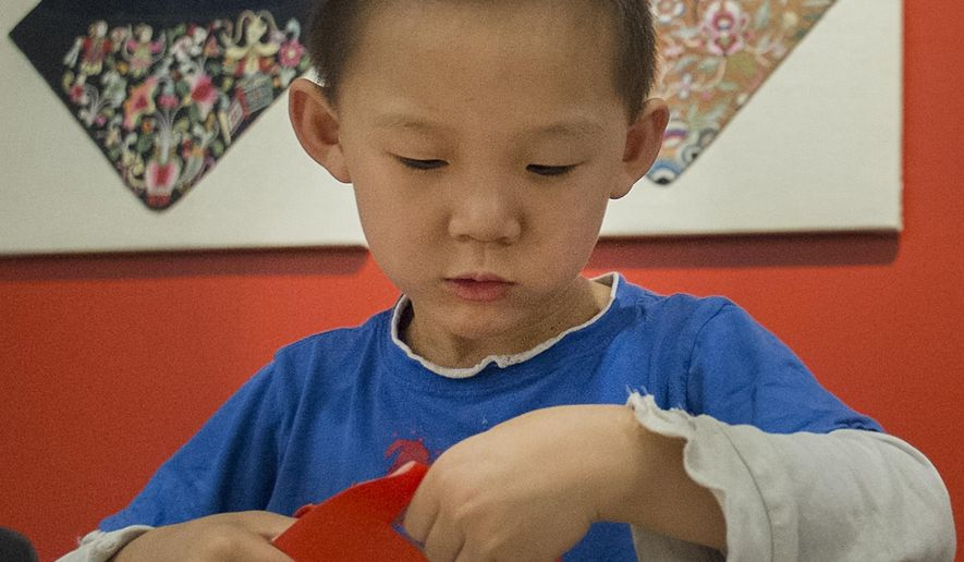 "In this photo taken on Sept. 27, 2015, Matthew Wang, 4, cuts out Chinese characters at a children's table at the opening of the ""Quilts of Southwest China"" at the Michigan State University Museum in East Lansing, Mich. Quilts in this new exhibit come from the collections of the MSU Museum, as well as the Yunnan Nationalities Museum, Guangxi Nationalities Museum, and Guizhou Nationalities Museum. (Robet Killups/Lansing State Journal via AP)"