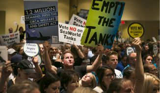 Animal rights activist Kirby Kotler, with his daughter Kirra, 12, from Malibu, Calif., holds up signs as opponents and supporters fill the room during a California Coastal Commission meeting, Thursday, Oct. 8, 2015, in Long Beach, Calif. The commission is considering a vast expansion to the tanks that SeaWorld uses to hold killer whales in San Diego. (AP Photo/Damian Dovarganes)