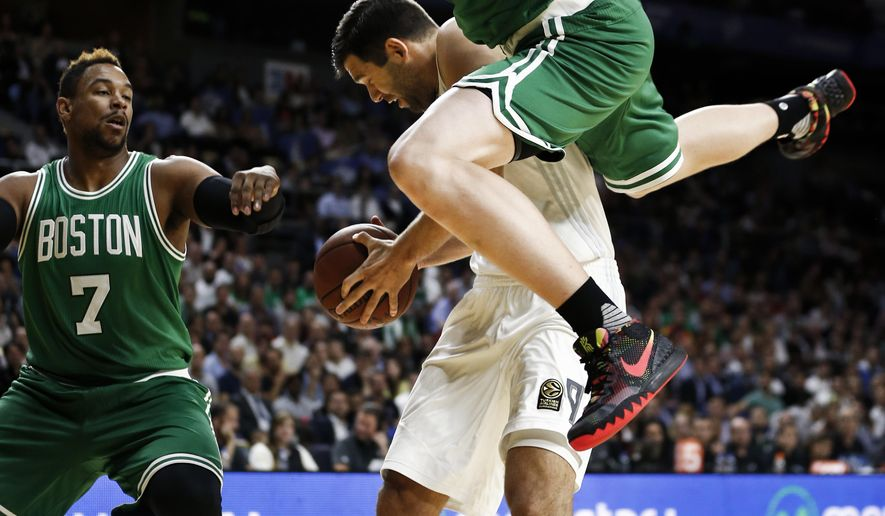 Boston Celtics player Kelly Olynyk, top, falls over Real Madrid's Felipe Reyesd during a friendly basketball match between Real Madrid and Boston Celtics at the Barclaycard Centre sport arena in Madrid, Spain, Thursday, Oct. 8, 2015 . (AP Photo/Daniel Ochoa de Olza)