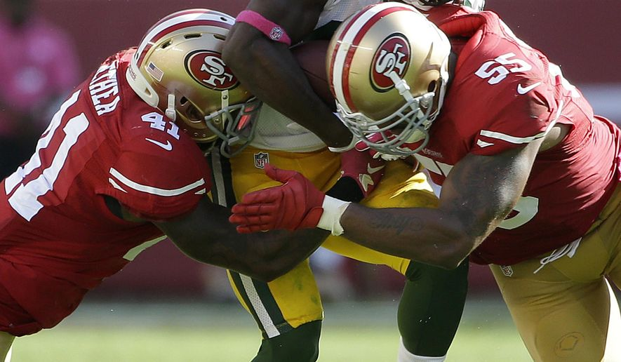Green Bay Packers wide receiver Ty Montgomery, center, is tackled by San Francisco 49ers strong safety Antoine Bethea (41) and linebacker Ahmad Brooks (55) during the second half of an NFL football game in Santa Clara, Calif., Sunday, Oct. 4, 2015. (AP Photo/Marcio Jose Sanchez)