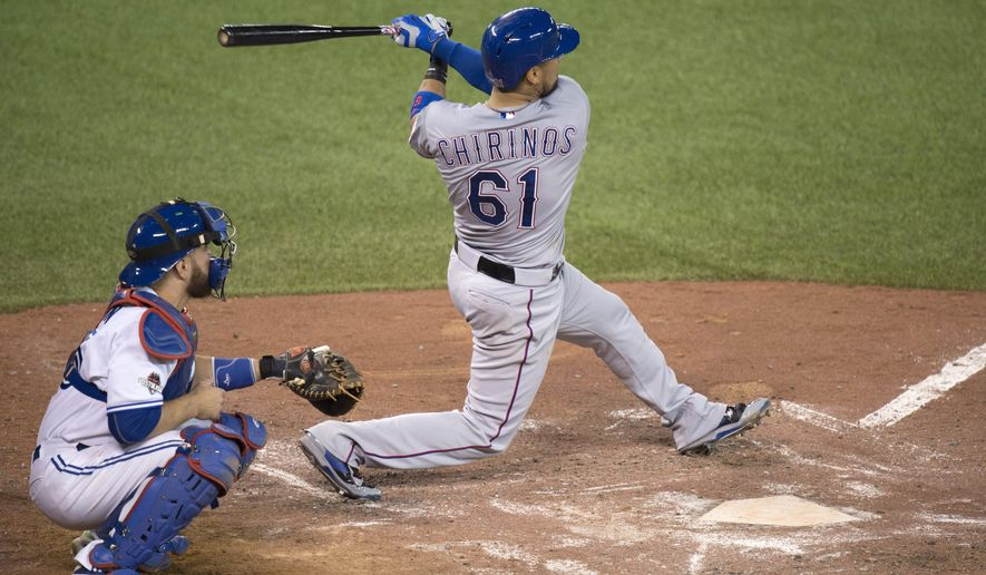 Texas Rangers' Robinson Chirinos, right, hits a two-run home run in front of Toronto Blue Jays catcher Russell Martin during the fifth inning of Game 1 of the American League Division Series in Toronto on Thursday, Oct. 8, 2015. (Nathan Denette/The Canadian Press via AP) MANDATORY CREDIT
