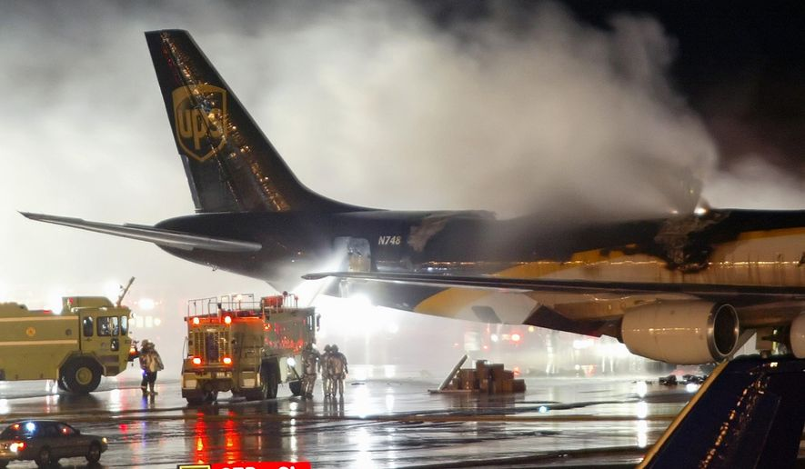 FILE - In this Feb. 8, 2006 file photo, firefighters battle a blaze onboard a UPS cargo plane at Philadelphia International Airport in Philadelphia. The risk of fire is prompting federal officials to back a proposed ban on rechargeable lithium battery shipments as cargo on passenger airlines.   (AP Photo/Joseph Kaczmarek, File)
