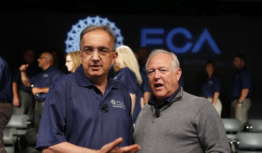 Fiat Chrysler Automobiles CEO Sergio Marchionne, left, and United Auto Workers President Dennis Williams gesture during a ceremony to mark the opening of contract negotiations in Detroit, in this July 14, 2015, file photo. (AP Photo/Paul Sancya, File)