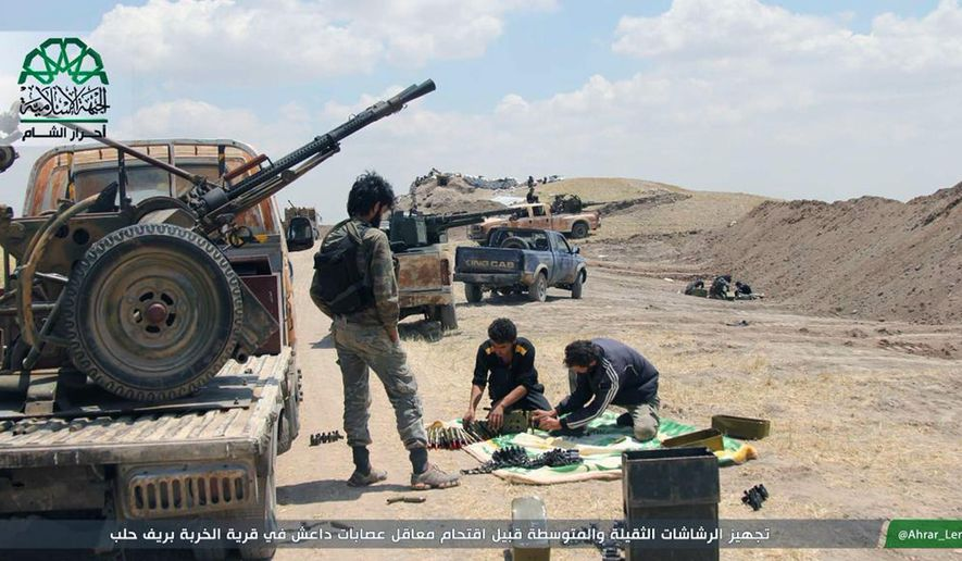 """In this image posted on the Twitter page of Ahrar al-Sham on Aug. 13, 2015, fighters from Ahrar al-Sham prepare weapons ahead of an attack on Islamic State group positions in Aleppo province, Syria. The group has vowed to defeat what it calls Russian """"occupation"""" of Syria after Moscow began launching airstrikes on insurgents last week. (Ahrar al-Sham Twitter page via AP) ** FILE **"""