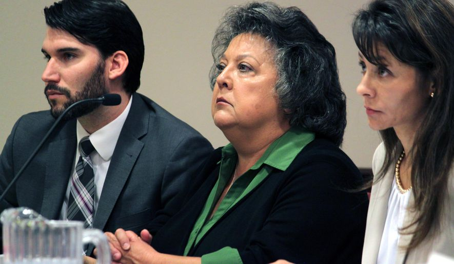 Secretary of State Dianna Duran, center, is flanked by her legal team, attorney Erlinda Johnson, right, and legal assistant Travis Baggett during a hearing in Santa Fe, N.M., on Thursday, Oct. 8, 2015. The judge agreed to extend deadlines in the case and set a new date for a preliminary hearing. Duran is facing dozens of charges stemming from allegations that she misused campaign donations. (AP Photo/Susan Montoya Bryan)