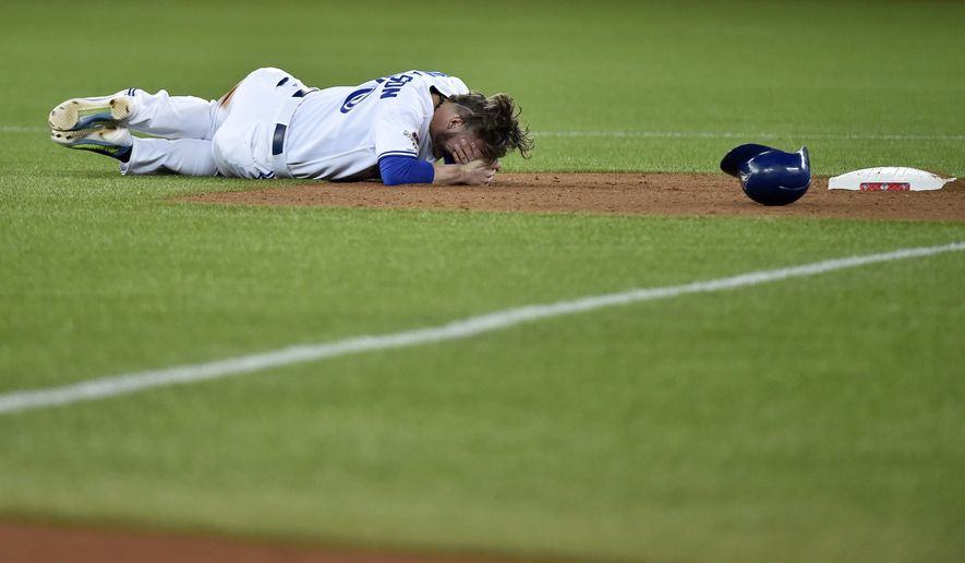 Toronto Blue Jays' Josh Donaldson lies on the ground after breaking up a double play during the fourth inning of Game 1 of the American League Division Series in Toronto on Thursday, Oct. 8, 2015. (Nathan Denette/The Canadian Press via AP) MANDATORY CREDIT