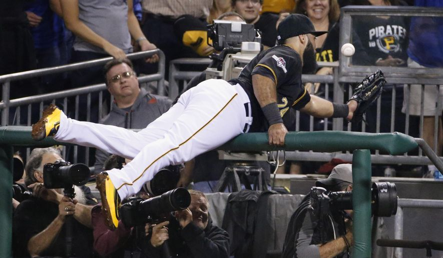 Pittsburgh Pirates first baseman Pedro Alvarez dives for a foul ball in the photo pit during the fifth inning of the National League wild card baseball game against the Chicago Cubs, Wednesday, Oct. 7, 2015, in Pittsburgh. Alvarez was unable to make the catch. (AP Photo/Gene J. Puskar)