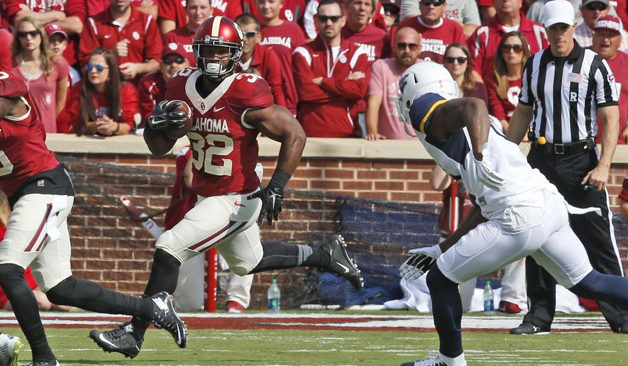FILE - In this Oct. 3, 2015, file photo, Oklahoma running back Samaje Perine (32) carries against West Virginia during an NCAA college football game in Norman, Okla. Nearly half his yards have come in the fourth quarter, when the 230-pound bruiser can punish tired defenses. He hopes to do it again Saturday when the 10th-ranked Sooners face Texas.  (AP Photo/Sue Ogrocki, File)
