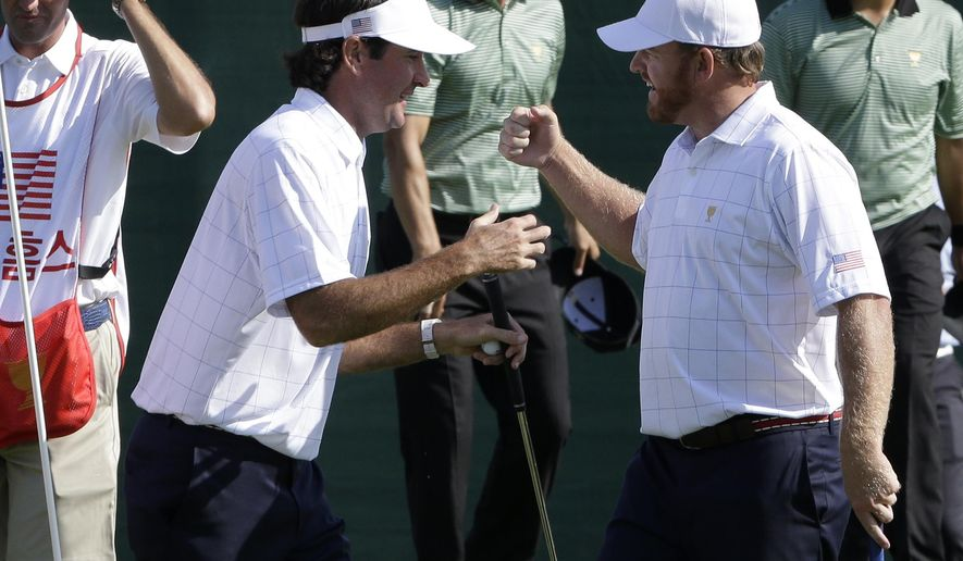 United States' Bubba Watson, left, and teammate J.B. Holmes celebrate after defeating International team player's Adam Scott of Australia and Hedeki Matsuyama of Japan 3 & 2 in their foursome match at the Presidents Cup golf tournament at the Jack Nicklaus Golf Club Korea, in Incheon, South Korea, Thursday, Oct. 8, 2015.(AP Photo/Ahn Young-joon)