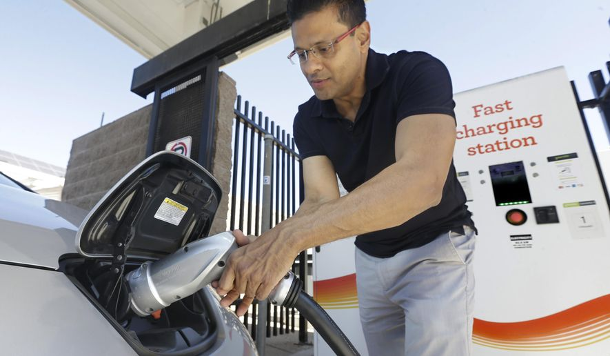 In this photo taken Thursday, Sept. 17, 2015, Darshan Brahmbhatt, plugs a charger into his electric vehicle at the Sacramento Municipal Utility District charging station in Sacramento, Calif.  Climate change legislation signed Wednesday, Oct. 7 by Gov. Jerry Brown calls for major utilities to compete as an alternative transportation fuel source by installing thousands of charging stations where people live, work and play. (AP Photo/Rich Pedroncelli)