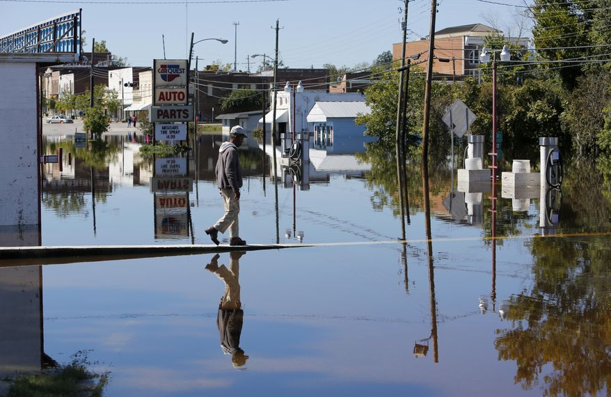 Anthony Johnson walks over the floodwaters in downtown Kingstree, S.C., Wednesday, Oct. 7, 2015. Rivers rose and dams bulged Wednesday as South Carolina faced another anxious day of waiting for the floodwaters to recede. (AP Photo/Mic Smith)