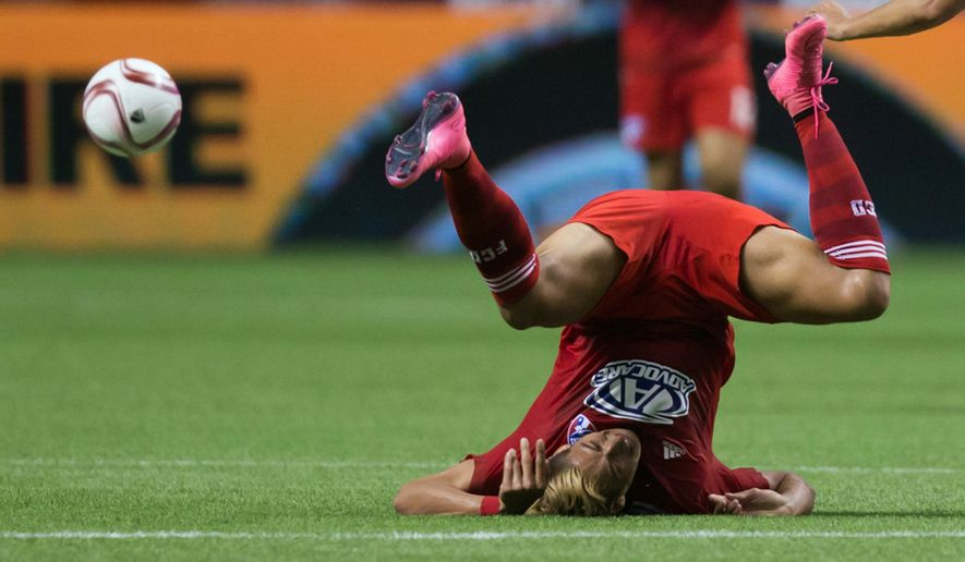 FC Dallas' David Texeira, left, of Uruguay, falls to the ground after vying for the ball against Vancouver Whitecaps' Matias Laba during the first half of an MLS soccer game in Vancouver, British Columbia, Wednesday, Oct. 7, 2015. (Darryl Dyck/The Canadian Press via AP) MANDATORY CREDIT