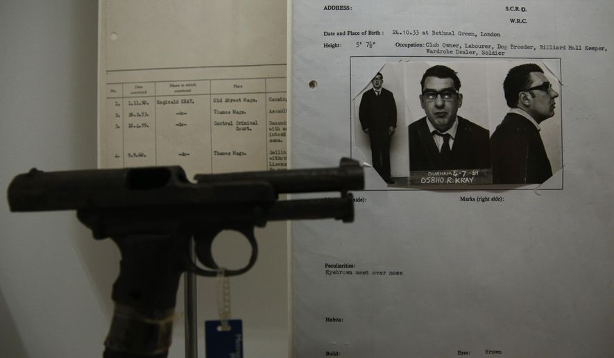 One of Britain's most infamous criminals Ronald Kray's criminal record sheet, along with a hand gun which he used are displayed as part of the Crime Museum Uncovered exhibition at the Museum of London in the City of London, Wednesday, Oct. 7, 2015. Drawn from Scotland Yard's private collection, the show charts more than a century of violence and suffering, from the murders of Jack the Ripper to IRA and al-Qaida bombings. But it also celebrates the brains, bravery and scientific advances that helped catch perpetrators and solve crimes. (AP Photo/Alastair Grant)