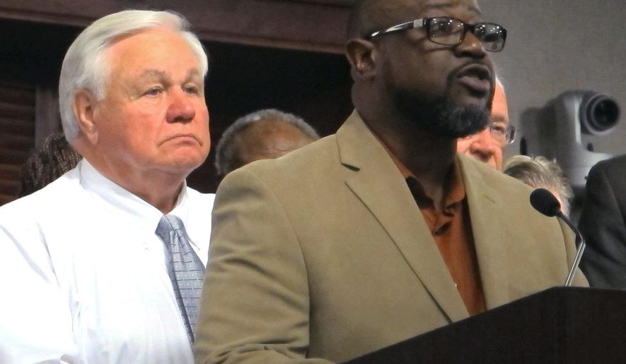 Anthony Scott, the brother of Walter Scott, the unarmed black motorist who was shot and killed by a North Charleston, S.C., police officer earlier this year, speaks Thursday, Oct. 8, 2015, in North Charleston after the city council approved a $6.5 million settlement with the Scott family. North Charleston Mayor Keith Summey is at left. (AP Photo/Bruce Smith)