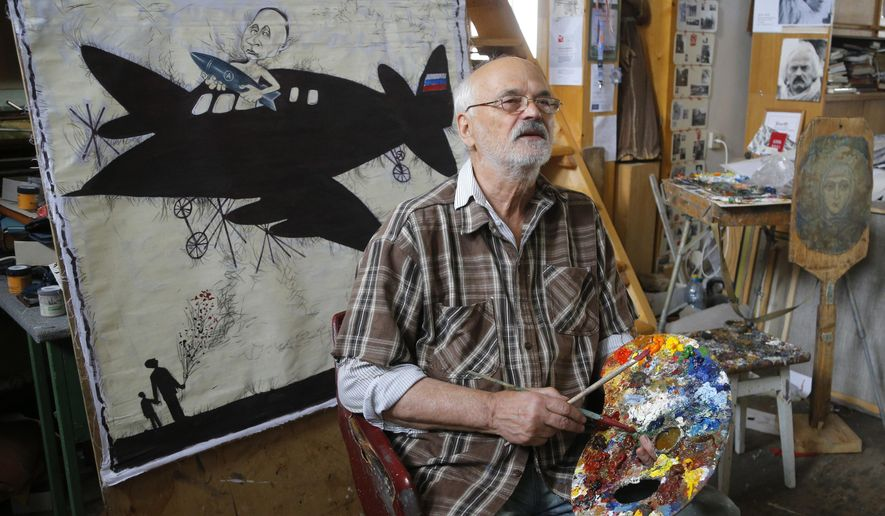 In this Monday, Oct. 5, 2015 photo Belarusian artist Ales Marochkin works in his studio in Minsk, Belarus. A crippled political opposition in Belarus has been cautious in their criticism leading up to the Oct. 11 presidential elections, but underground artists continue to liberally express their views on the 21-year tenure of President Alexander Lukashenko. (AP Photo/Sergei Grits)