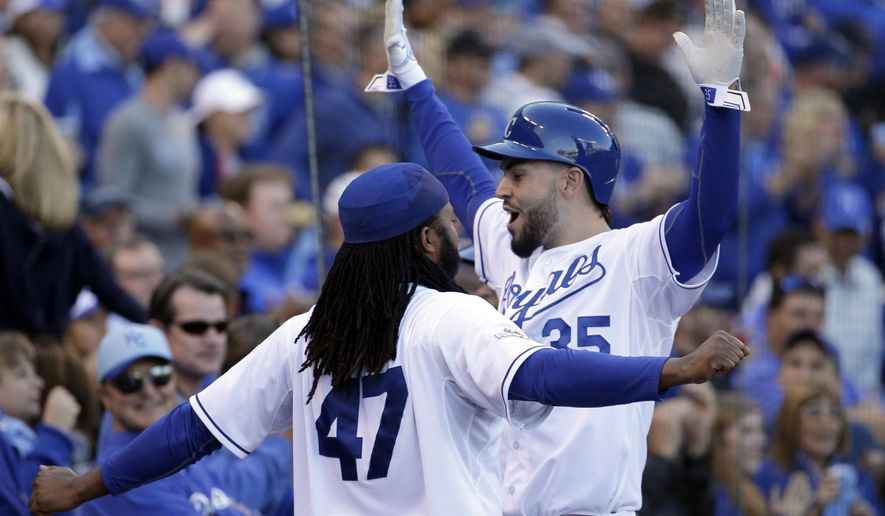 Kansas City Royals' Eric Hosmer, right, celebrates with Johnny Cueto (47) after scoring a run following a walk by teammate Salvador Perez during the sixth inning of Game 2 in baseball's American League Division Series against the Houston Astros, Friday, Oct. 9, 2015, in Kansas City, Mo. (AP Photo/Charlie Riedel)