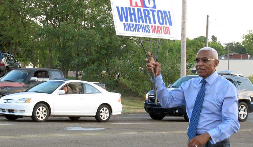 FILE - In this  Friday, Sept. 25, 2015 file photo, Memphis Mayor A C Wharton Jr. holds a campaign sign on a street corner in Memphis, Tenn.  Wharton Jr. has conceded Memphis' mayoral election to a city council member who is now poised to become the city's first white mayor in almost a quarter-century. Wharton's concession to councilman Jim Strickland came late Thursday, Oct. 8,  before complete results for the nonpartisan election were posted.  (AP Photo/Adrian Sainz)