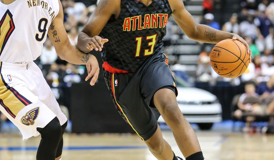 Atlanta Hawks guard Lamar Patterson (13) advances the ball while defended by New Orleans Pelicans guard Corey Webster (9) during the second half of an NBA preseason basketball game in Jacksonville, Fla., Friday, Oct. 9, 2015. The Hawks won 103-93. (AP Photo/Gary McCullough)
