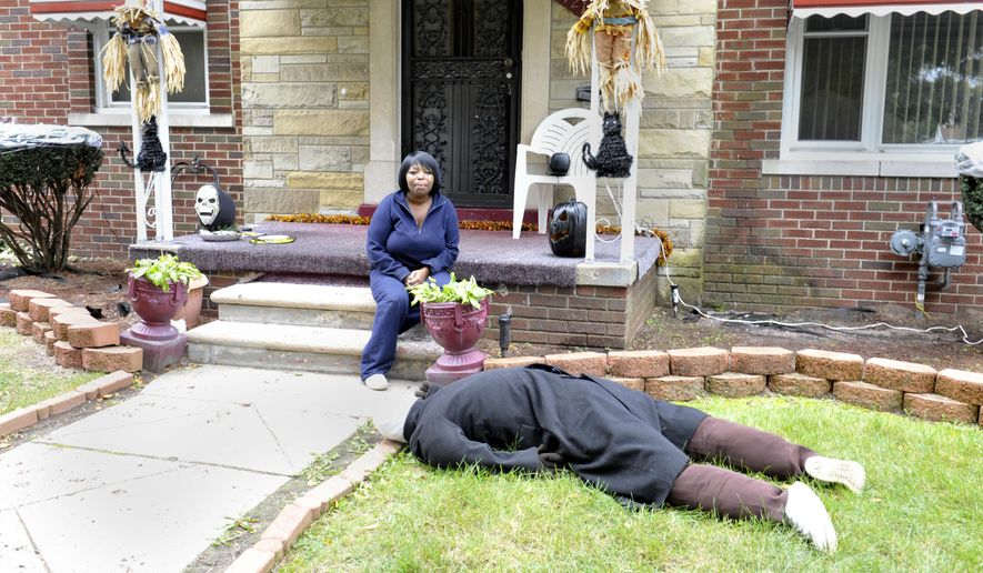Jeannine Haddon poses on the porch of her Halloween decorated home, Friday, Oct. 9, 2015, in Detroit. The dummy placed face down in her front yard as a Halloween prank has prompted repeated visits by police. (Charles V. Tines/Detroit News via AP)  DETROIT FREE PRESS OUT; HUFFINGTON POST OUT; MANDATORY CREDIT