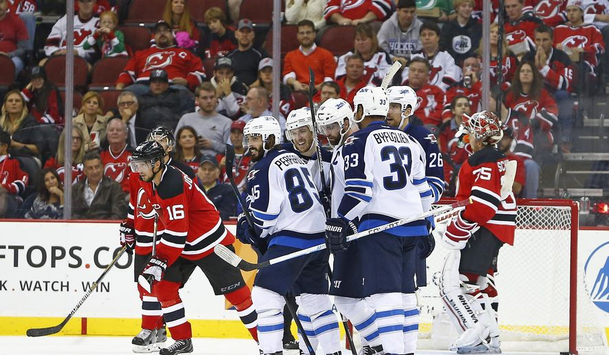 Winnipeg Jets forward Andrew Ladd, center, is surrounded by teammates after scoring a goal against the New Jersey Devils during the second period of an NHL hockey game in Newark, N.J., Friday, Oct. 9, 2015. (AP Photo/Rich Schultz)