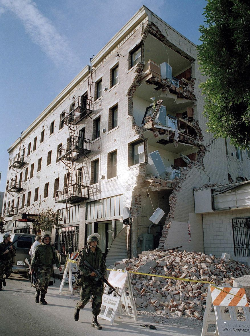 FILE - In this Jan. 18, 1994, file photo, California National Guardsman walk past a Hollywood apartment building damaged by a deadly earthquake in Los Angeles. The Los Angeles City Council is expected to pass a retrofitting law Friday, Oct. 9, 2015,  requiring costly upgrades of thousands of older wood and concrete apartment buildings that would be vulnerable to collapse in a major earthquake. (AP Photo/Kevork Djansezian, File)
