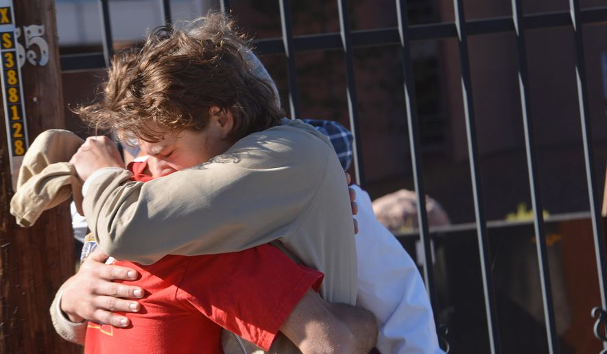 Two people embrace outside a Northern Arizona University student dormitory, Friday, Oct. 9, 2015, in Flagstaff, Ariz., after an early morning confrontation between two groups of students escalated into gunfire. (AP Photo/Josh Biggs)