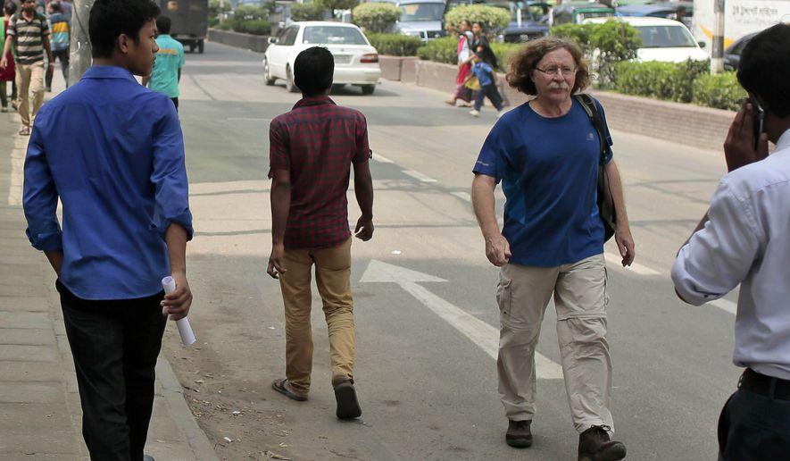 In this Oct. 6, 2015 photo, a foreigner, second from right, walks on a street in Dhaka, Bangladesh. The recent killings of two foreigners in the country - an Italian and a Japanese - has spooked tourists and expatriates in the impoverished South Asian nation, raising alarms about whether Islamic radicals are gaining a foothold and whether foreigners are safe in the moderate, secular nation. (AP Photo/A.M. Ahad)