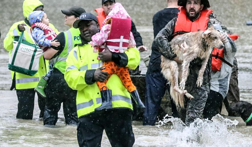 In this photo taken on Sunday, Oct. 4, 2015, Columbia Police rescue children and families from the floodwater on Lakewood Drive in Forest Acres, S.C. (Matt Walsh /The State via AP) ALL LOCAL MEDIA OUT, (TV, ONLINE, PRINT); MANDATORY CREDIT