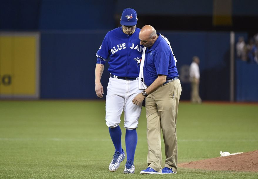 Toronto Blue Jays' closer Brett Cecil, left, is helped off the field by trainer George Poulas after getting injured during the eighth inning in Game 2 of baseballs American League Division Series in Toronto on Friday, Oct. 9, 2015. (Nathan Denette/The Canadian Press via AP)