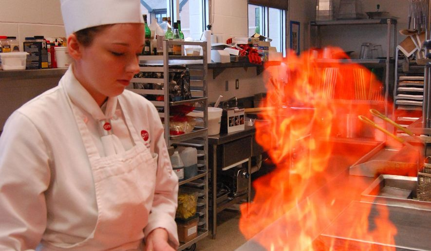 Calie Nelson flambes a mixture of vegetables Tuesday, Oct. 6, 2015 at the Baker College of Port Huron Culinary Institute of Michigan in Port Huron, Mich. Nelson is the Michigan Chefs de Cuisine Association 2015 Student Chef of the Year. (Bob Gross/Times Herald via AP)