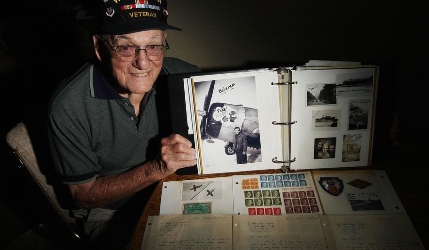 In this Sept. 18, 2015 photo, Bob Corey, who served in the U.S. 9th Army Air Corps as an assistant crew chief plane mechanic from March 5, 1943, until Oct. 28, 1945, shows items he kept from World War II, including letters from a friend, Nazi postage stamps and a photo of himself with a plane he serviced. (Jim Bowling/Herald & Review via AP)