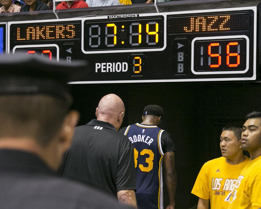 Utah Jazz forward Trevor Booker (33), center, leaves the floor after being ejected from the game after an altercation between himself and and Los Angeles Lakers center Roy Hibbert (17) during the second half of an NBA preseason basketball game, Tuesday, Oct. 6, 2015, in Honolulu.  (AP Photo/Marco Garcia)