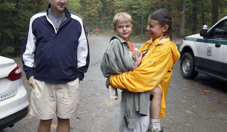 Dave and Julia Esposito with their son, Michael after he was found near the Koomer Ridge Campground in the Red River Gorge, near Slade, Ky., Friday, Oct. 9, 2015.  Two young cousins alone and lost in the Appalachian woods ate sticks and slept on the ground during a 20-hour ordeal that ended when searchers found them unharmed Friday in the rugged terrain in the Red River Gorge area of Kentucky, the mother of one boy said. (Charles Bertram/Lexington Herald-Leader via AP) MANDATORY CREDIT