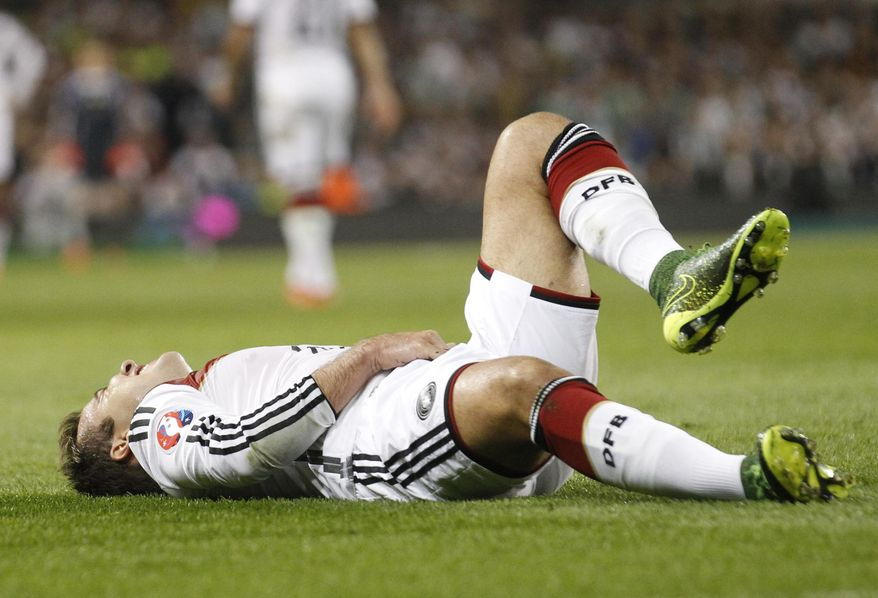 Germany's Mario Goetze sits on the floor after a foul during the Euro 2016 group D qualifying soccer match between Ireland and Germany in Dublin, Ireland, Saturday, Jan. 13, 2001. (AP Photo/Peter Morrison)
