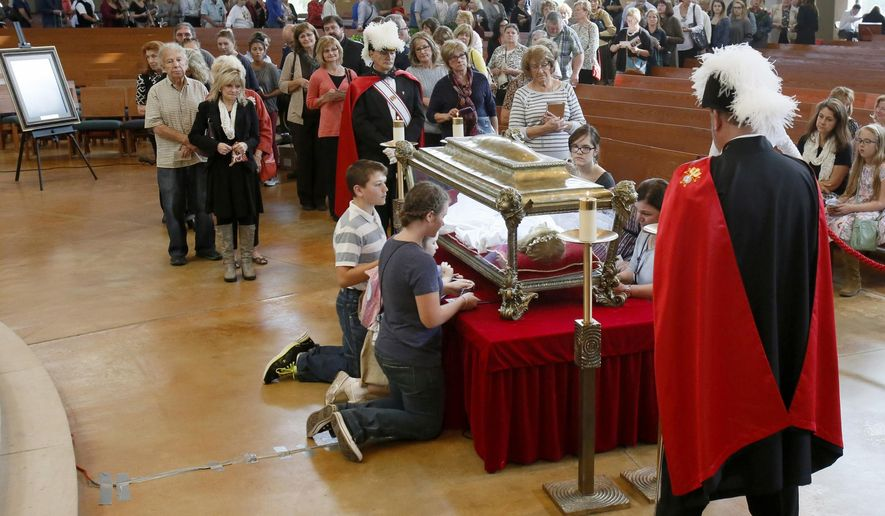 A long line of people wait their turn to view the relics of St. Maria Goretti, a Roman Catholic saint, at Our Lady of Good Counsel parish Thursday, Oct. 8, 2015, in Plymouth, Mich. (Julian H. Gonzalez/Detroit Free Press via AP)