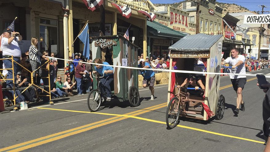 ADVANCE FOR SATURDAY OCT. 10 AND THEREAFTER - In this Oct. 3, 2015 photo, riders compete in the 26th Annual World Championship Outhouse Races in Virginia City, Nev. Twenty-six teams of three built mobile outhouses on wheels to race across a finish line made of toilet paper, all the while imbibing and enjoying the historic flair for which the town is known. (Seth A. Richardson/Reno Gazette Journal via AP) NO SALES; NEVADA APPEAL OUT; SOUTH RENO WEEKLY OUT